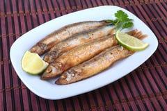 油炸小鱼毛鳞鱼和切的柠檬在白色板材 对啤酒的好快餐 免版税库存图片