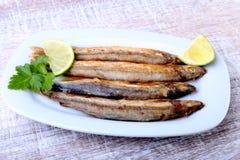 油炸小鱼毛鳞鱼和切的柠檬在白色板材 对啤酒的好快餐 库存照片