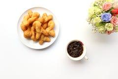油炸面团棍子顶视图有冷的coffe和花的 免版税库存照片