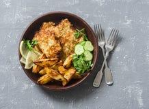 油炸鱼和大蒜烘烤了在灰色背景,顶视图的土豆 英国筹码鱼快餐桌传统木 免版税库存图片