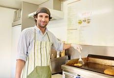油煎一个新鲜的汉堡包小馅饼用乳酪的男性油炸烹饪 库存照片