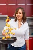 油煎土豆的少妇 免版税库存图片