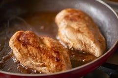 油煎在平底锅的两个鸡胸脯片断 免版税库存照片
