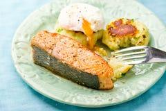 油煎的三文鱼用土豆小馅饼和荷包蛋 免版税库存照片