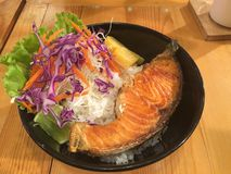 油煎的三文鱼用在黑盘的米 免版税库存图片