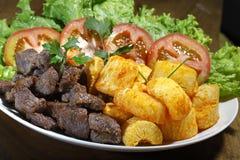 油煎的丝兰、肉和沙拉 免版税库存照片