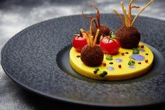 油煎的丸子用在的蕃茄在一个黑色的盘子的土豆 免版税库存图片