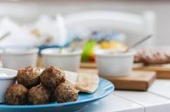 油煎的丸子用白汁和平的蛋糕-在一块蓝色板材的传统希腊午餐在餐馆 免版税库存图片