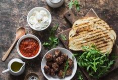 油煎的丸子,西红柿酱,无盐干酪,芝麻菜,烤了在一张木桌,顶视图上的面包热的三明治成份 Deliciou 免版税库存图片