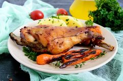 油煎的兔子腿,装饰煮的土豆,烤红萝卜-在板材 免版税图库摄影