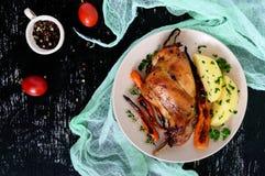 油煎的兔子腿,装饰煮的土豆,烤红萝卜-在黑暗的背景的一块板材 库存照片