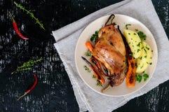 油煎的兔子腿,装饰煮的土豆,烤红萝卜-在黑暗的背景的一块板材 图库摄影