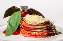 油煎的切的茄子用辣味番茄酱和草本在白色板材 库存图片
