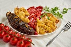 油煎的土豆、茄子、用叉子在白色板材关闭装饰的甜椒和花椰菜,新鲜的西红柿 库存照片