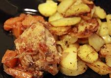 油煎的土豆和油煎的鱼和黑色的盘子 免版税图库摄影