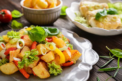 油煎的土豆沙拉用莴苣、胡椒、葱和被烘烤的鱼fi 库存图片