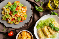 油煎的土豆沙拉用莴苣、胡椒、葱和被烘烤的鱼fi 图库摄影