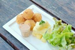 油煎的土豆球和沙拉在木桌上 免版税库存图片