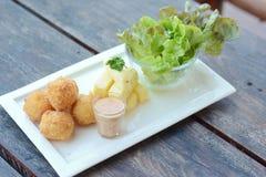 油煎的土豆球和沙拉在木桌上 库存图片