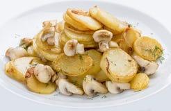 油煎的土豆用在一块白色板材的蘑菇 盘祖母腌制传统俄国的s 免版税库存照片