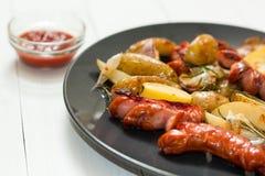 油煎的土豆用在板材的香肠 图库摄影