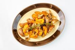 油煎的土豆用在白色背景的蘑菇 免版税库存图片