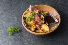油煎的土豆用开胃烟肉和调味汁在一块木板材 库存图片