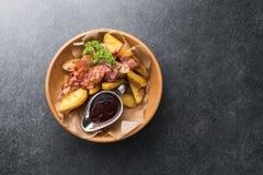 油煎的土豆用开胃烟肉和调味汁在一块木板材 免版税库存图片