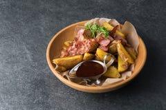 油煎的土豆用开胃烟肉和调味汁在一块木板材 免版税库存照片