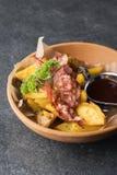 油煎的土豆用开胃烟肉和调味汁在一块木板材 免版税图库摄影
