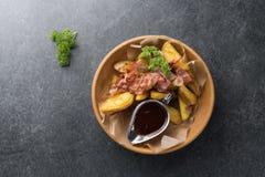 油煎的土豆用开胃烟肉和调味汁在一块木板材 库存照片