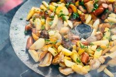 油煎的土豆用烤概念的肉和香肠烹调在开火 野餐在周末 免版税库存图片