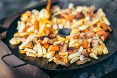 油煎的土豆用烤概念的肉和香肠烹调在开火 野餐在周末 免版税库存照片