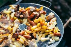 油煎的土豆用烤概念的肉和香肠烹调在开火 野餐在周末 图库摄影