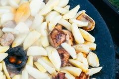 油煎的土豆用烤概念的肉和香肠烹调在开火 野餐在周末 库存照片