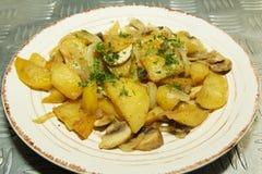 油煎的土豆用草本和蘑菇 库存照片