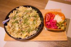 油煎的土豆用蘑菇和葱在平底锅 盐味的蔬菜 桌在餐馆,承办宴席 免版税库存照片