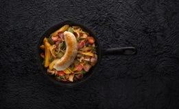 油煎的土豆用香肠在老生铁平底锅服务 库存图片