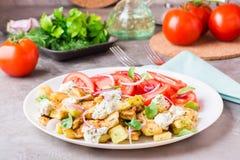 油煎的夏南瓜用希腊白软干酪、蕃茄、草本和葱 图库摄影