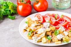 油煎的夏南瓜用希腊白软干酪、蕃茄、草本和葱 免版税库存图片