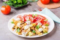 油煎的夏南瓜用希腊白软干酪、蕃茄、草本和葱 库存照片