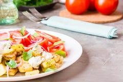 油煎的夏南瓜用希腊白软干酪、蕃茄、草本和葱 免版税图库摄影