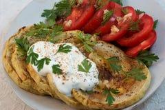 油煎的夏南瓜用蕃茄、大蒜、草本和酸性稀奶油 免版税库存照片