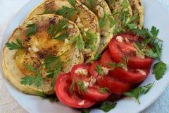 油煎的夏南瓜用蕃茄、大蒜和草本 免版税库存图片