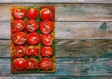 油煎的夏南瓜用蕃茄和大蒜在玻璃切割委员会木减速火箭的背景的,顶视图特写镜头 库存图片