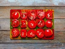 油煎的夏南瓜用蕃茄和大蒜在玻璃切割委员会木减速火箭的背景的,顶视图 免版税库存图片