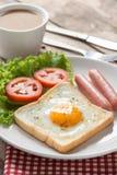 油煎的多士用鸡蛋、香肠和杯子咖啡 库存照片