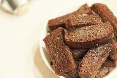 油煎的大蒜油煎方型小面包片,在一块白色板材的黑面包 库存图片