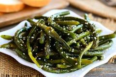 油煎的大蒜箭头开胃菜 辣绿色大蒜箭头用香料和芝麻籽在板材 容易,便宜地和健康食谱 免版税库存图片