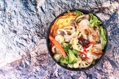 油煎的大面条用煎蛋卷冠上了在汤的混杂的菜 图库摄影